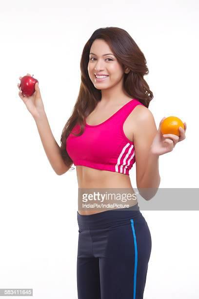 Portrait of woman holding apple and orange