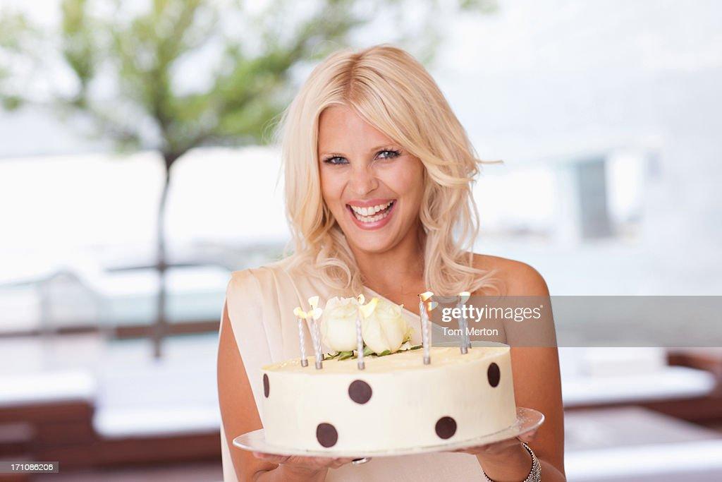 Portrait of woman holding birthday cake : Stock Photo