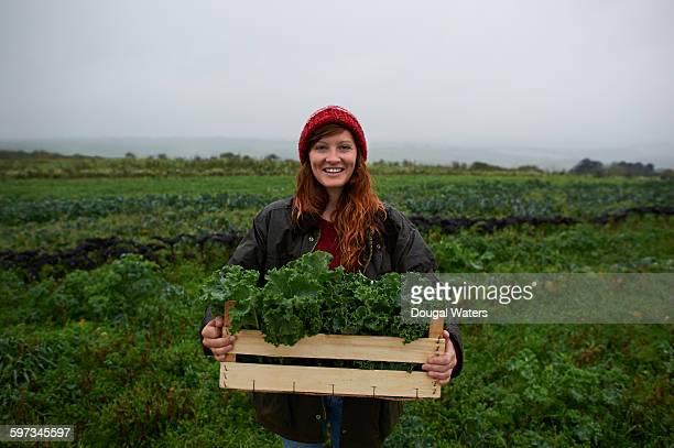 Portrait of woman holding box of kale on farm.