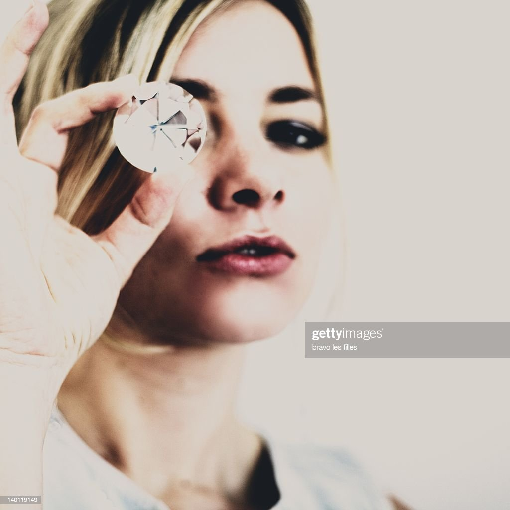 Portrait of woman holding diamond in front of eye : Stock Photo