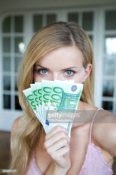 Portrait of woman holding Euro notes, smiling