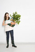 Portrait of woman holding potted orange tree