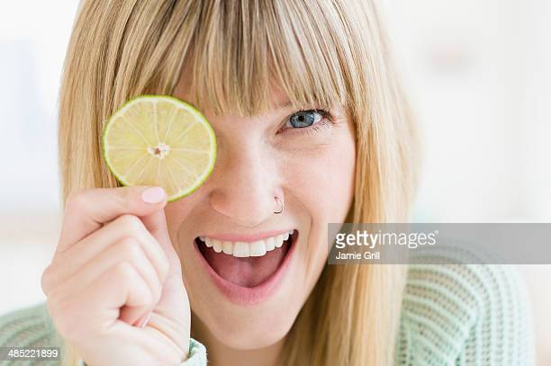Portrait of woman holding slice of lime