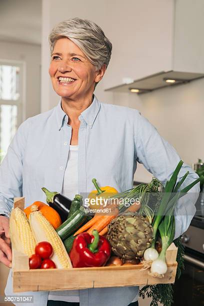 Portrait of woman holding wooden box of vegetables