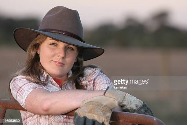 Portrait of woman in a cowboy hat and gloves by an iron gate