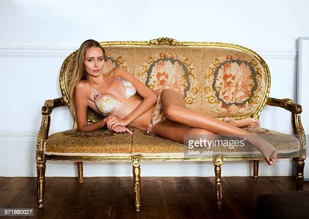 Portrait of woman in bikini lying on sofa