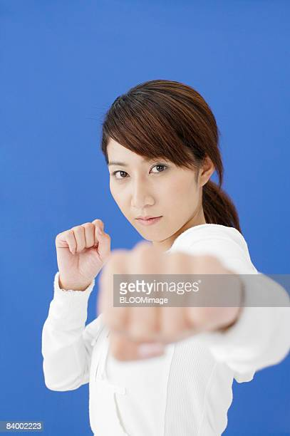 Portrait of woman in fighting stance, close-up, studio shot
