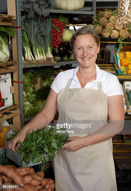 Portrait of woman in front of vegetable stall