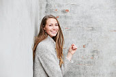Portrait of woman in gray fashion against wall