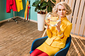 portrait of woman in retro clothing with golden fish in aquarium sitting on chair at colorful apartment, doll house concept