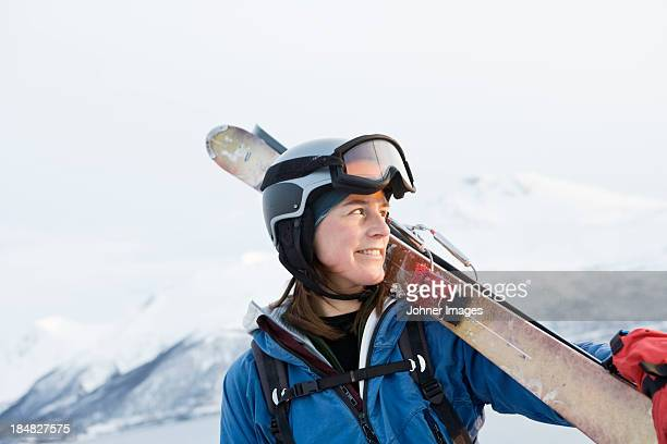 Portrait of woman in ski-wear holding skis