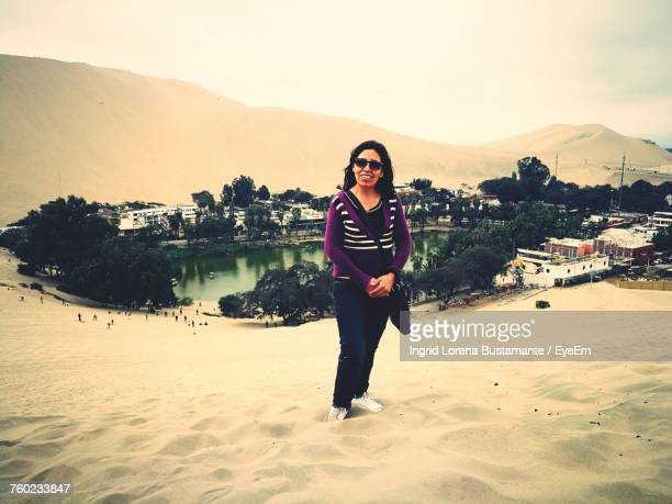 Portrait Of Woman In Sunglasses Standing On Desert At Oasis