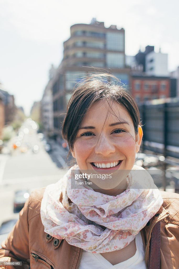 Portrait of woman in the city, smiling.