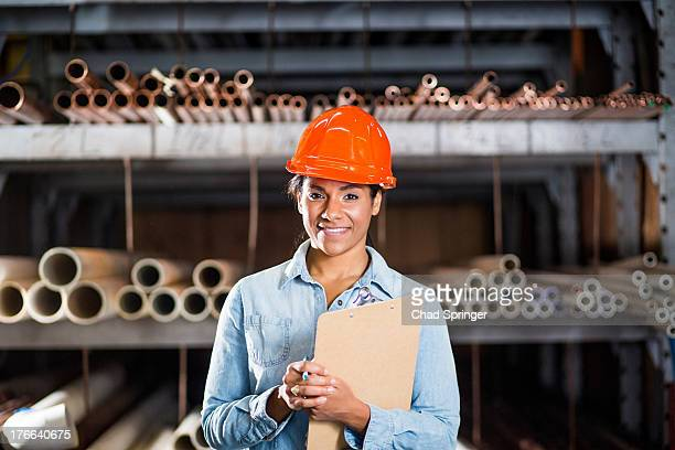 Portrait of woman in warehouse with clipboard