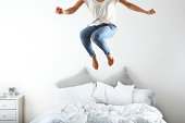 Portrait of woman jumping on bed