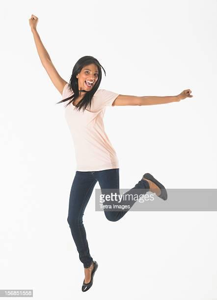 Portrait of woman jumping, studio shot
