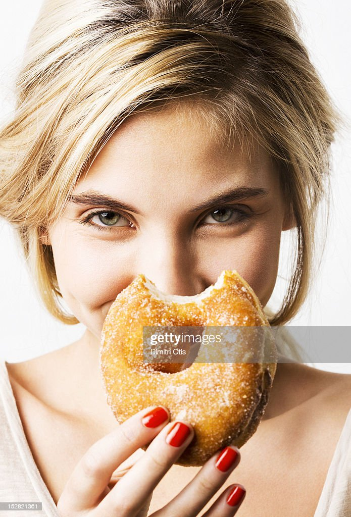 Portrait of woman laughing, holding bitten donut : Stock Photo