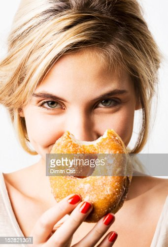 Portrait of woman laughing, holding bitten donut