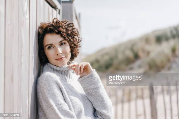 Portrait of woman leaning against beach hut