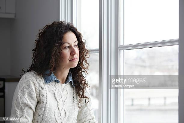 Portrait of woman looking out window