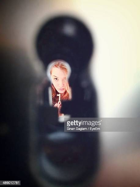 Portrait of woman looking through keyhole