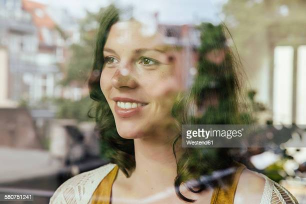 Portrait of woman looking through the window