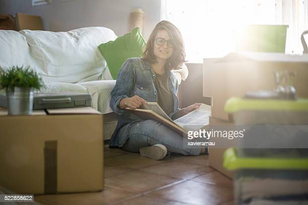Portrait of woman looking to a photo album moving home