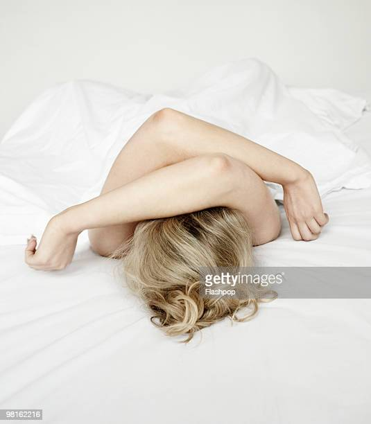 Portrait of woman lying on bed covering her eyes