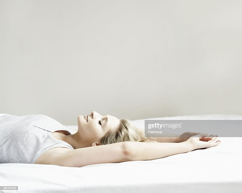 Portrait of woman lying on bed : Stock Photo