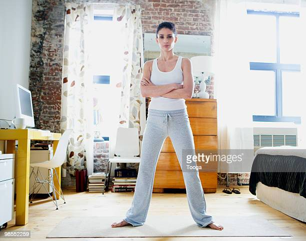 Portrait of woman on yoga mat in apartment