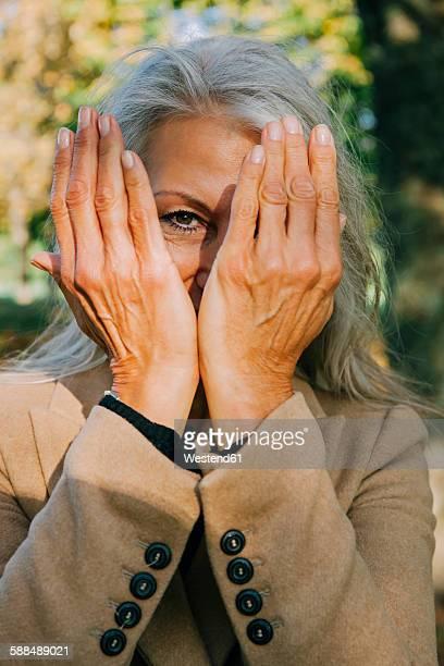 Portrait of woman peeking through her hands