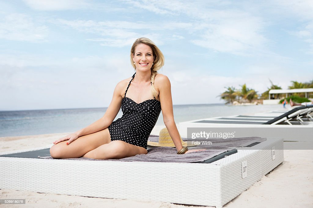Portrait of woman posing on deck chair on beach : Photo