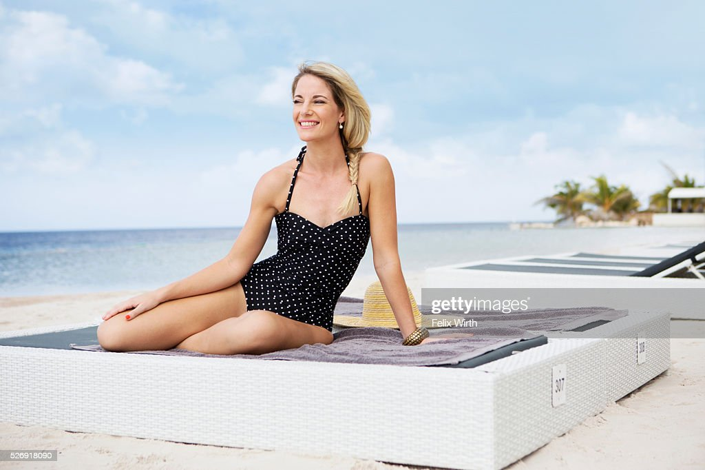 Portrait of woman posing on deck chair on beach : Stock-Foto