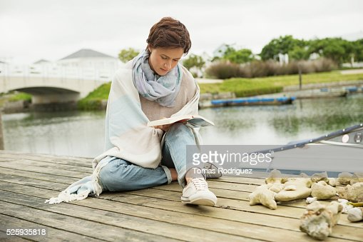Portrait of woman reading book on deck : Stock Photo