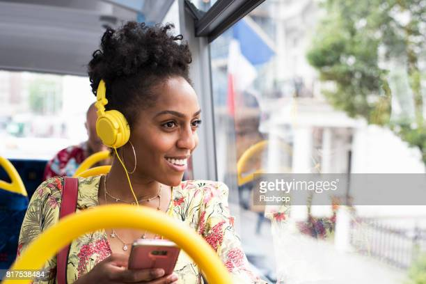 Portrait of woman relaxing on a bus wearing headphones