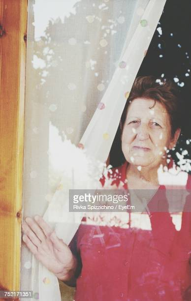 Portrait Of Woman Seen Through Glass Window At Home