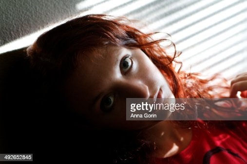 Portrait of woman shadowed by window blinds : Stock Photo