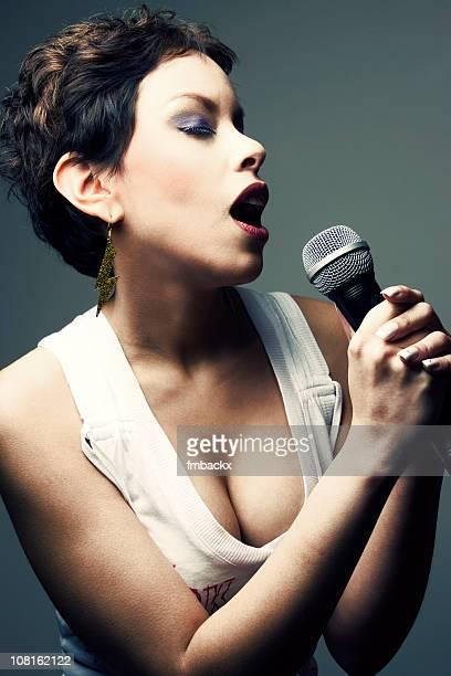 Porträt der Frau singt in ein Mikrofon