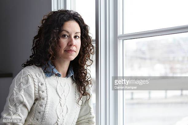 portrait of woman sitting at window