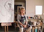 Portrait of woman sitting by sketch in art class