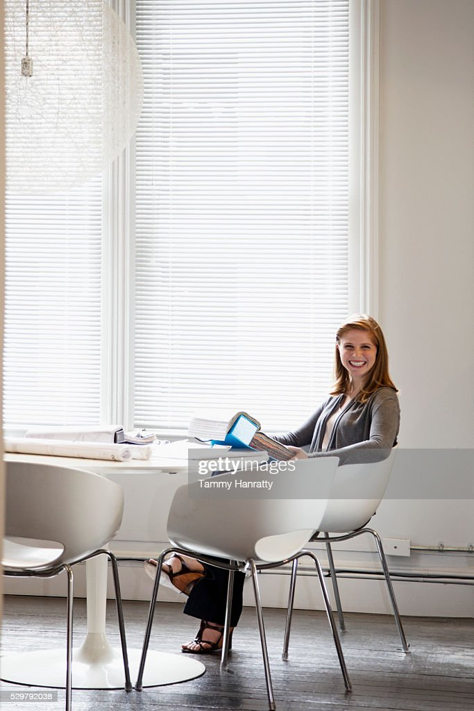 Portrait of woman sitting in office : Stock Photo