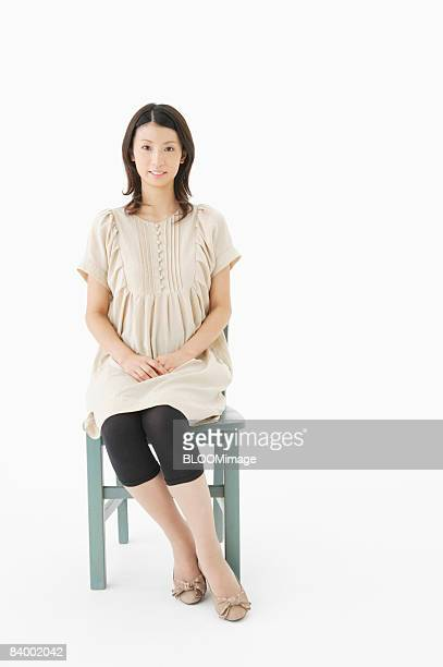 Portrait of woman sitting on chair, studio shot