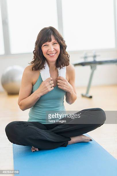 Portrait of woman sitting on mat in gym, Jersey City, New Jersey, USA