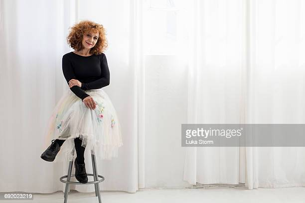 Portrait of woman sitting on stool looking at camera
