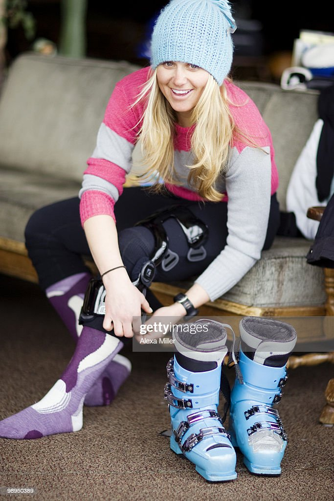 Portrait of  woman skier adjusting knee brace.
