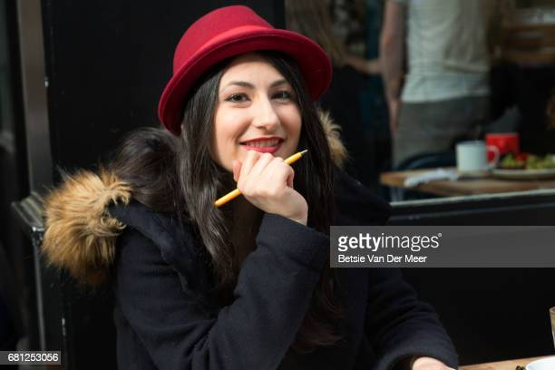 Portrait of woman smiling, wearing hat, sitting in cafe.