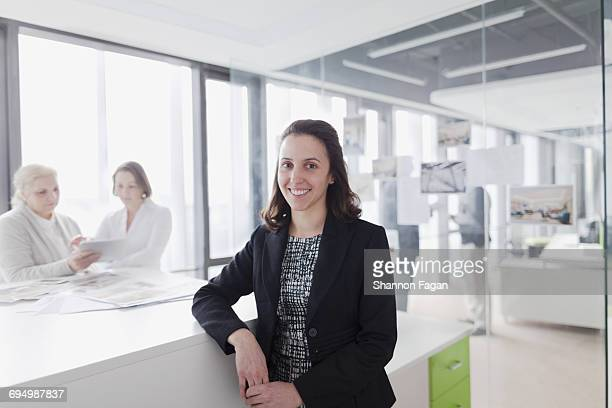 Portrait of woman standing at work desk in office