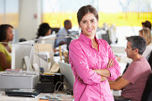 Portrait Of Woman Standing In Busy Creative Office Smiling To Camera
