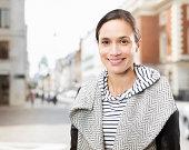 portrait of woman standing in city street.