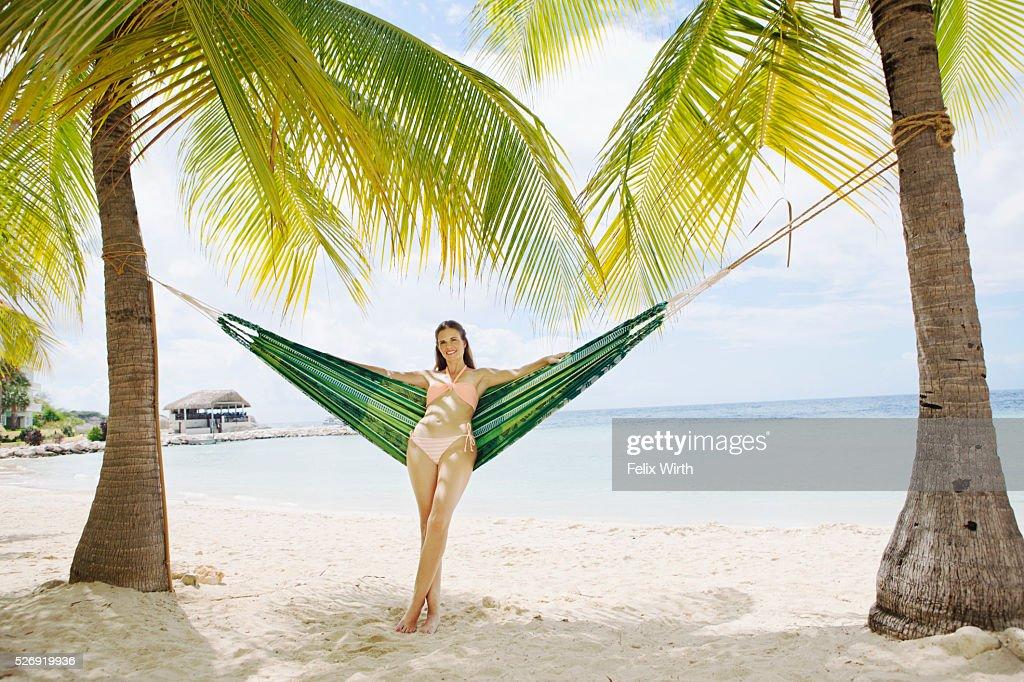 Portrait of woman standing near hammock on beach : Stock Photo